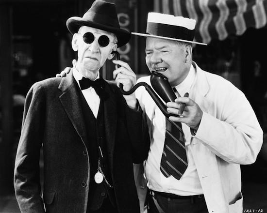 W.C. Fields speaks into an old man's hearing trumpet. Movie still. --- Image by © Bettmann/CORBIS